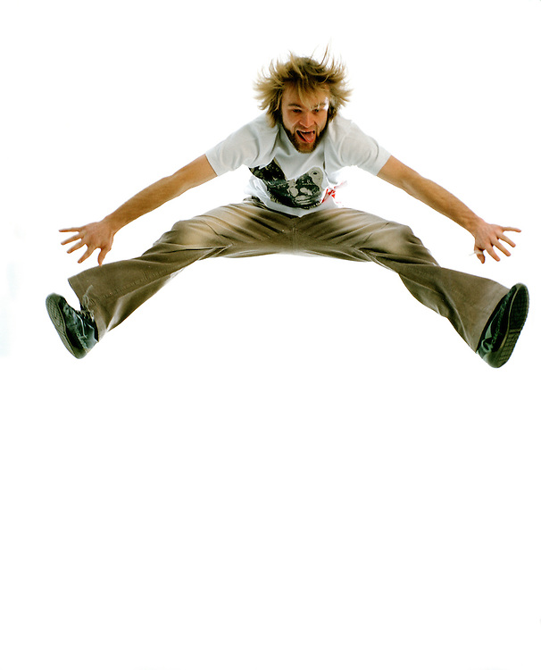 Lifestyle portrait of a male jumping in the air doing the splits