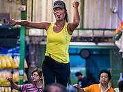 11 AUGUST 2016 - BANGKOK, THAILAND:    The instructor leads an aerobics class in Pak Khlong Talat, better known as the Bangkok Flower Market. Public exercise classes are common throughout Thailand. Most of the participants in the exercise class in the Bangkok flower market are older adults, although the class is open to everyone.       PHOTO BY JACK KURTZ