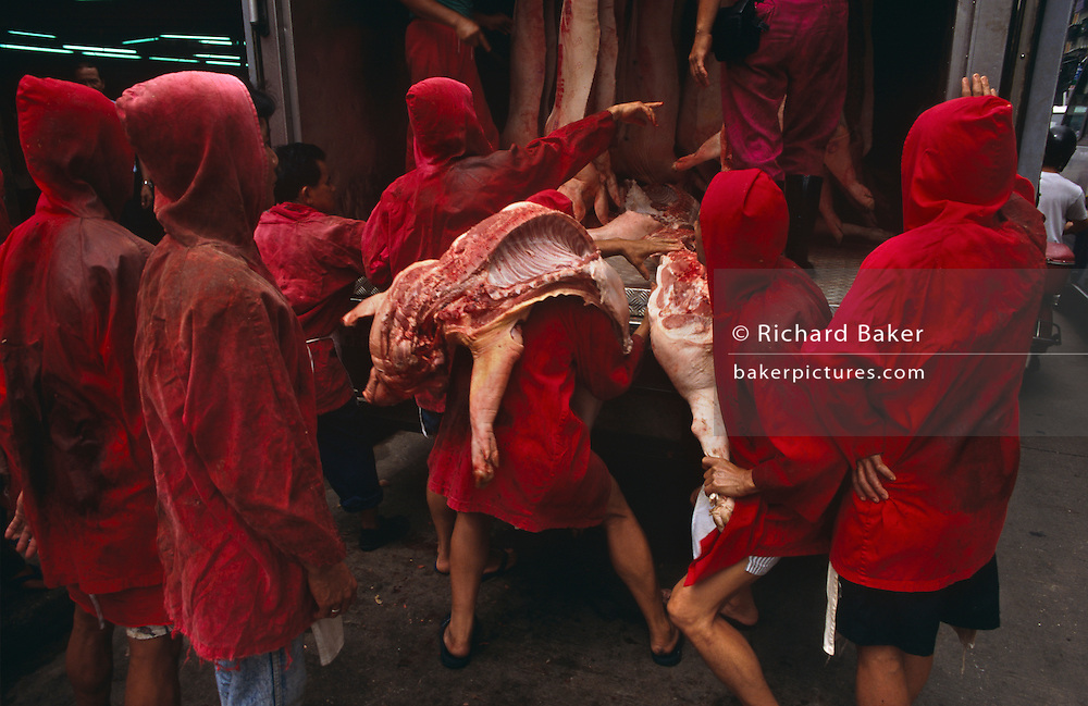 A group of red uniformed meat market traders manhandle joints of pork from the back of a meat wagon at Macau's main meat market, on the Rua Sul do Mercado de Sao Domingos, just off the Avenida de Almeida Ribeiro, in Central Macau, 1994.