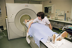 Imaging superintendent Radiographer preparing male patient for CT scan,