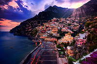 """""""Positano burst of color at sunset""""…<br /> <br /> After an exhilarating drive along the high cliffs on the Amalfi coast from Sorrento down to Positano, I found myself in sensory overload with its beauty and photogenic appeal.  After circling around the entire village and its cliffside three times on Positano's only street, which was a single lane winding down from the top and back up and over to where I began, I finally found the parking garage by the hotel, about 2/3rds up the facing village in this image.  The climb down the winding road and steep staircases made for quite a workout in the hot late May sun.  Reaching the beach and marina, I forgot about my exhaustion and could not capture enough of Positano's plush beauty; however, the large amount of tourists and bright sun did not allow for ideal conditions.  Walking the length of the beach, I found a very, very steep staircase leading straight up to a large veranda at the Albergo California.  Taking an exhaustive seat on a plush lounge chair with a perfect view to watch the sunset behind the Amalfi Cliffs, I was taken back by a pleasant Italian (Positano) waiter from the hotel offering a towel, ice water, and drinks for the evening.  I expressed that I was not staying at the hotel, but he didn't seem to mind and proceeded to educate me on the culture of this historic resort village.  The sunset was being coy and didn't appear to cooperate, but during opportune moments it mystified the cloud arrangement and contributed just enough rays of light and color to satisfy a weary photographer."""