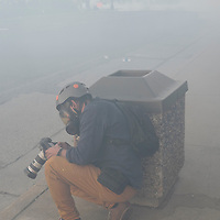 Reuters photojournalist Carlos Barria takes cover behind a trash can as members of the Minnesota State Patrol launch tear gas and less-lethal rounds at protesters and media near the Minneapolis Police fifth precinct after a white police officer was caught on a bystander's video pressing his knee into the neck of African-American man George Floyd, who later died at a hospital, in Minneapolis, Minnesota, U.S. May 30, 2020. REUTERS/Adam Bettcher