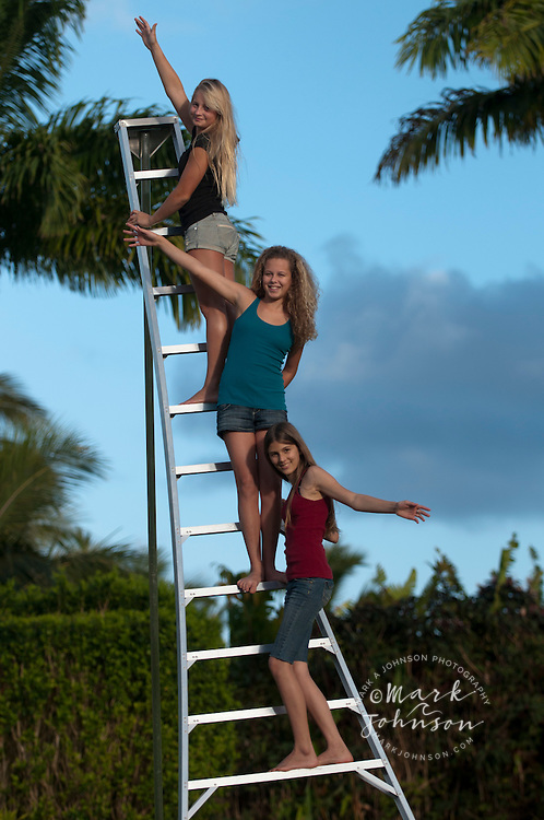 Teenage girls on ladder, Kauai, Hawaii people ****Model Release available