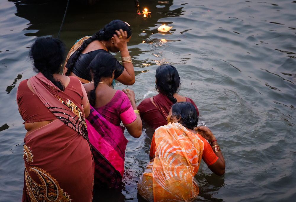 VARANASI, INDIA - CIRCA NOVEMBER 2016: Women worshiping and bathing in the Ganges river. Varanasi is the spiritual capital of India, the holiest of the seven sacred cities and with that many rituals and offerings are performed daily by priests and hindus.
