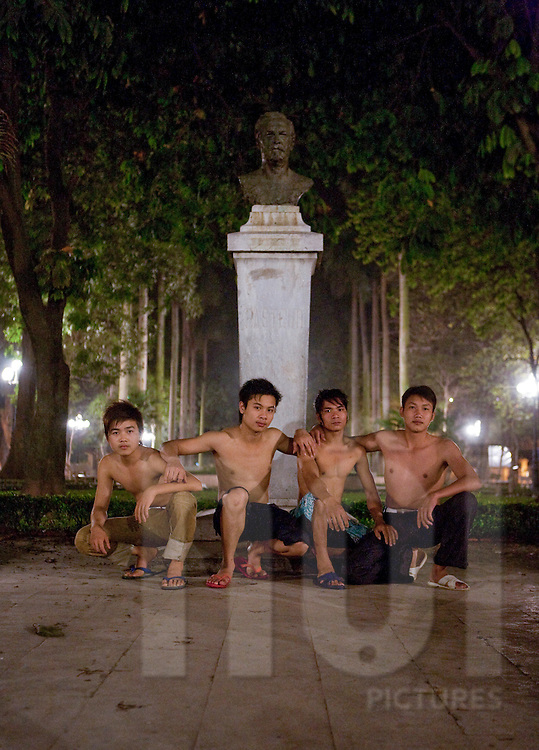 A group of young hanoian bia hoi (restaurant serving cheap beer) workers pose shirtless in front of a bust of Louis Pasteur. Hanoi, Vietnam, Southeast Asia