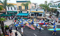 June 20, 2017 - Huntington Beach, California, USA - The first wave of nearly 600 surfers make their way along Main Street in downtown Huntington Beach as the procession heads to the ocean to create the world's largest paddle out ''Circle of Honor'' in Huntington Beach Tuesday morning, June  20, 2017. (Photo by Mark Rightmire, Orange County Register/SCNG) (Credit Image: © Mark Rightmire, Mark Rightmire/The Orange County Register via ZUMA Wire)
