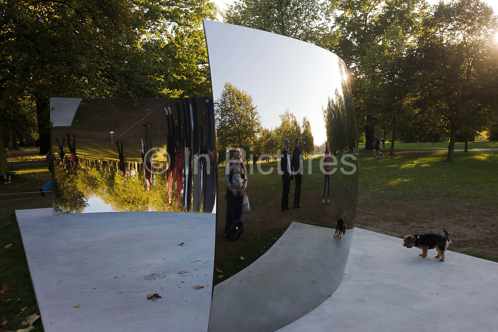 Admirers and a pet dog look at their reflections in artist Anish Kapoor's artwork called the C-Curve, part of his Turning the World Upside Down is seen at the Serpentine Gallery. The Royal Parks and the Serpentine Gallery presented a major exhibition of large- scale outdoor sculptures by acclaimed London-based artist Anish Kapoor in Kensington Gardens. The free exhibition showcased a series of major recent works never before shown together in London. Constructed from highly reflective stainless steel, the giant curved mirror surfaces will create illusory distortions of the surroundings and will be visible across large distances, creating new vistas in this famous and much-loved setting. The sculptures were sited to contrast and reflect the changing colours, foliage and weather in Kensington Gardens.