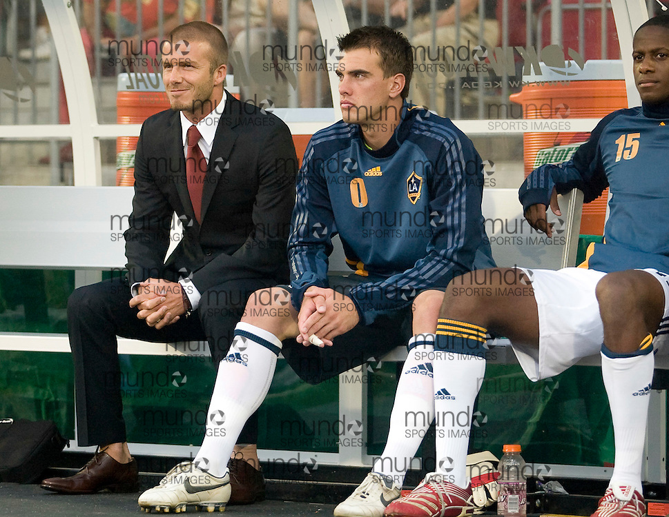 David Beckham sits with Los Angeles Galaxy back up goal keeper Steve Cronin as he sits on the bench during the Galaxy's match against the Toronto FC on 05 August, 2007 in Toronto, Ontario, Canada. .AFP PHOTO/GEOFF ROBINS