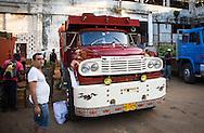 Man smoking as workers offload produce, Mercado Agropecuario Cuatros Caminos, Havana, Cuba
