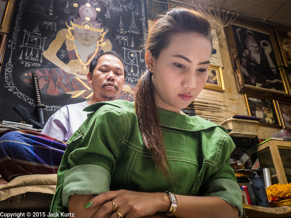 """25 MAY 2015 - BANGKOK, THAILAND:  AUEN, a Thai woman who sells cosmetics, prays while she gets a Sak Yant tattoo from Ajarn Neng Onnut in his tattoo parlor in Bangkok. Sak Yant (Thai for """"tattoos of mystical drawings"""" sak=tattoo, yantra=mystical drawing) tattoos are popular throughout Thailand, Cambodia, Laos and Myanmar. The tattoos are believed to impart magical powers to the people who have them. People get the tattoos to address specific needs. For example, a business person would get a tattoo to make his business successful, and a soldier would get a tattoo to help him in battle. The tattoos are blessed by monks or people who have magical powers. Ajarn Neng, a revered tattoo master in Bangkok, uses stainless steel needles to tattoo, other tattoo masters use bamboo needles. The tattoos are growing in popularity with tourists, but Thai religious leaders try to discourage tattoo masters from giving tourists tattoos for ornamental reasons.       PHOTO BY JACK KURTZ"""