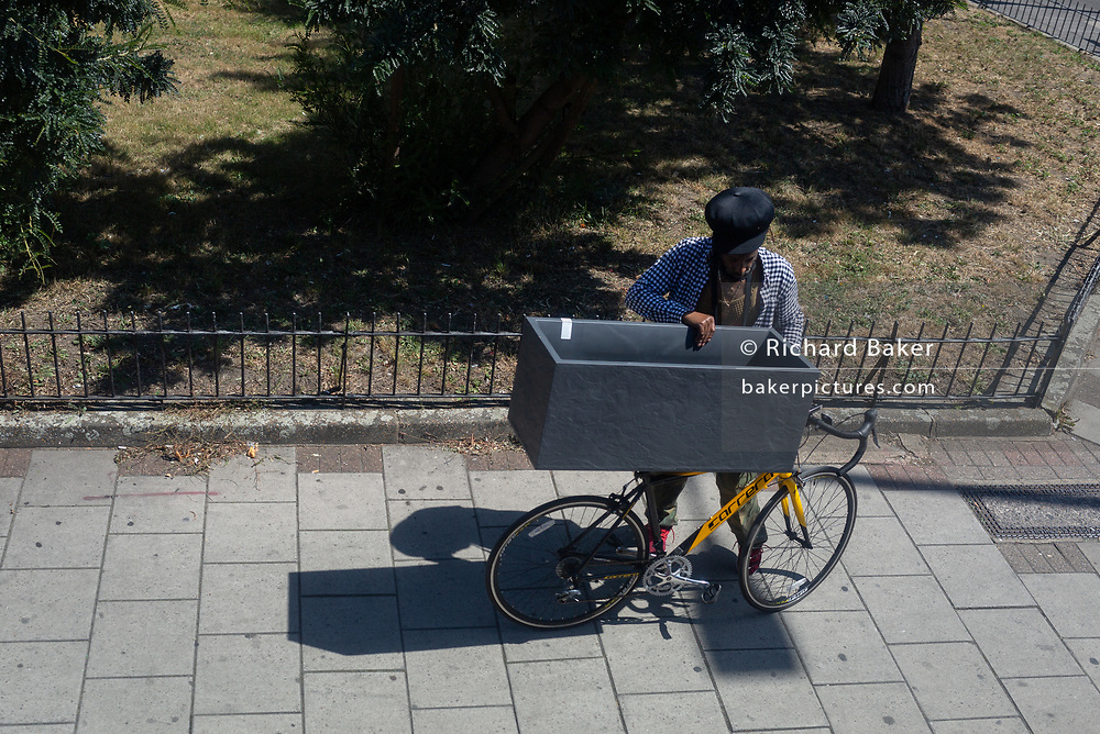A south London man stops to look into the black box that he's been pushing perched on his bike saddles on the Walworth Road, on 31st July 2020, in London, England.