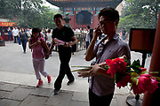 "Young man with flowers and incense at Yonghe Temple, also known as the ""Palace of Peace and Harmony Lama Temple"", the ""Yonghe Lamasery"", or - popularly - the ""Lama Temple"" is a temple and monastery of the Geluk School of Tibetan Buddhism located in the northeastern part of Beijing, China. It is one of the largest and most important Tibetan Buddhist monasteries in the world. The building and the artworks of the temple is a combination of Han Chinese and Tibetan styles."