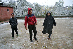 A Kashmiri young boys enjoying  snowfall in Srinagar, the summer capital of Indian controlled Kashmir. Kashmir witnessed its first snowfall.