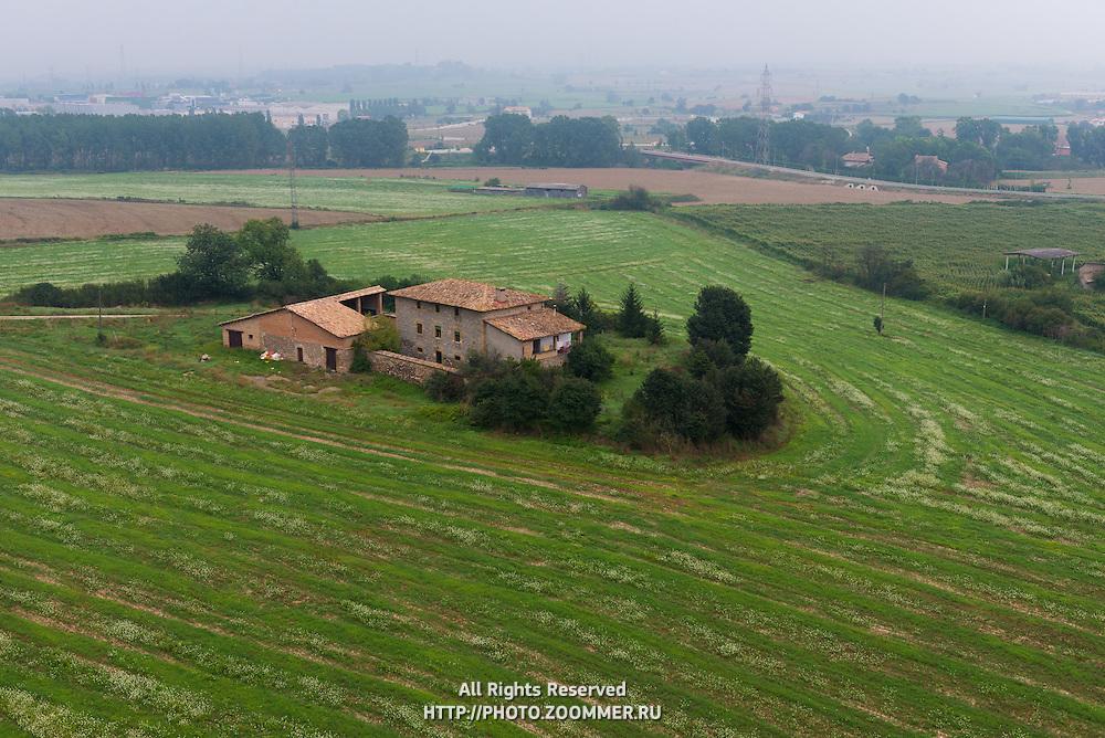 Small farm house among fields from air baloon near Vic, Spain