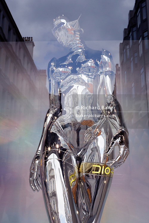 A highly-reflective silver-coloured mannequin in the window of the fashion brand Dior in New Bond Street, on 30th April 2019, in London, England