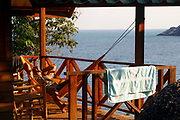 A traveler enjoys an afternoon siesta in a hammock at the origin beach huts. Hat Yuan Beach, Koh Phangnan, Thailand