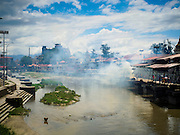 03 AUGUST 2015 - KATHMANDU, NEPAL: Smoke from the cremation ghats drifts over the Bagmati River at Pashupatinath, a complex of important Hindu temples in Kathmandu. The Bagmati River runs through the complex. It is Nepal's most holy river, and this stretch of the river is like Varanasi in India. The river bank is lined with cremation ghats. Many Hindus, from both Nepal and India, make pilgrimages to Pashupatinath.   PHOTO BY JACK KURTZ