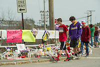 Teenagers observe the memorial set up along the Messer Street bridge throughout the day on Monday to remember Lily Johnson following the tragic accident on Friday afternoon.   (Karen Bobotas/for the Laconia Daily Sun)