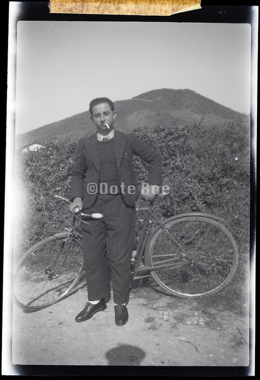 male adult person with a cigarette in the mouth and bicycle  in a rural mountain landscape
