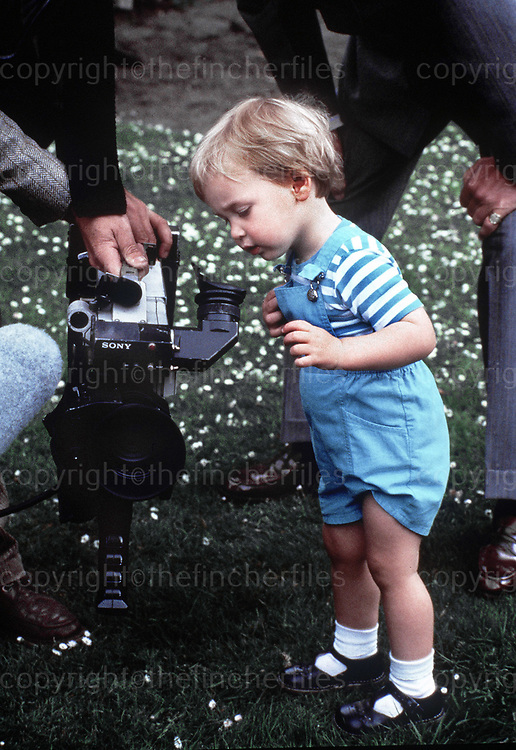 PRINCE WILLIAM SEEN IN THE GARDENS OF KENSINGTON PALACE WITH HIS PARENTS THE PRINCE AND PRINCESS OF WALES, FOR AN OFFICIAL PHOTO CALL.  MAY 1984. POOL PICTURES. HE IS SEEN LOOKING AT ONE OF THE MANY TV CAMERAS THERE FOR THE OCCASION.