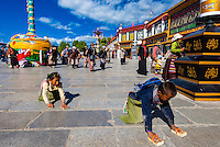 Tibetan children prostrating themselves epeatedly as they circumambulate through Barkhor Square and along The Barkhor (around the area of the Jokhang Temple), the most sacred temple in Tibet, Lhasa, Tibet, China.