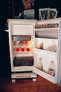 The Khuenkaew's refrigerator holds some soft drinks, eggs, a bag of meat. Thailand. The Khuenkaew family lives in a wooden 728-square-foot house on stilts, surrounded by rice fields in the Ban Muang Wa village, outside the northern town of Chiang Mai, in Thailand. Material World Project.