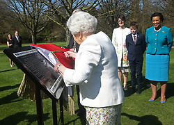 Queen Elizabeth II unveils a panel marking the walkway in Buckingham Palace gardens, London, in relation to the Commonwealth Walkway project.