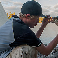 Ben Wiltsie examines a smallmouth bass he caught on Lake of the Woods, Ontario, Canada.