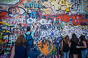 A visitor is spraying a heart to The Lennon Wall or John Lennon Wall, which is a wall in Prague, Czech Republic. Once a normal wall, since the 1980s it has been filled with John Lennon-inspired graffiti and pieces of lyrics from Beatles songs.