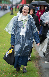© Licensed to London News Pictures. 26/08/2018. Dublin, Ireland. A nun dressed in a poncho arrives in wet weather for the vsit of Pope Francis to Phoenix Park Dublin. Pope Francis said mass to an estimated hundred thousand people. Pope Francis is the 266th Catholic Pope and current sovereign of the Vatican. Photo credit: Barry Cronin/LNP