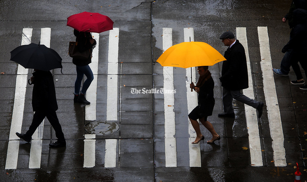 Pedestrians cross Sixth Avenue at Pine St. in downtown Seattle between heavy rain showers. (Ellen M. Banner / The Seattle Times)