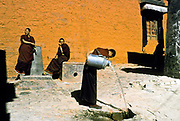 Monks who live at Tashilunpo Monastery carry water cans for their daily needs, Shigatze city, Tibet