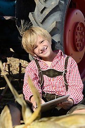 Boy with digital tablet and tractor on field, Bavaria, Germany