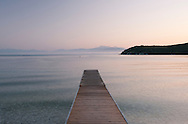 Mist at sunrise near mountains in Albania viewed from Avlaki beach on the northeast coast of Corfu, The Ionian Islands, The Greek Islands, Greece, Europe