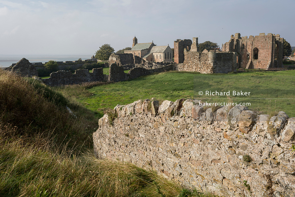 The landscape surrounding the early 12th century Lindisfarne Priory on Holy Island, on 27th September 2017, on Lindisfarne Island, Northumberland, England. The monastery of Lindisfarne was founded by Irish monk Saint Aidan, and the priory was founded before the end of 634 and Aidan remained there until his death in 651. The Holy Island of Lindisfarne, also known simply as Holy Island, is an island off the northeast coast of England. Holy Island has a recorded history from the 6th century AD; it was an important centre of Celtic and Anglo-saxon Christianity. After the Viking invasions and the Norman conquest of England, a priory was reestablished.