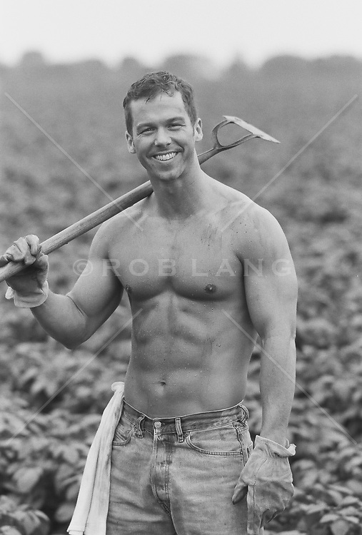 good looking shirtless man holding a hoe in a field