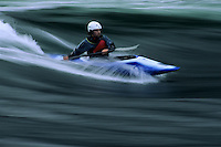 A kayaker surfs a wave at Blue Hill Falls in Blue Hill, Maine.  Panned for motion blur.