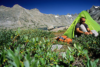 A young man sits at camp in Titcomb Basin, Wind River Range, Wyoming.