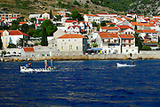 View of village of Bol from sea, with two small fishing boats in foreground. Island of Brac, Croatia