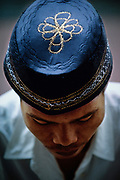 """Alone with his God, a worshipper wears an embroidered prayer cap called a """"songkok"""" or """"kopiah"""" at Jakarta's Istiqlal Mosque.  White caps signify that a Muslim has made the once-in-a-life-time pilgrimage to Mecca and Medina call the Hajj.  © Steve Raymer 2002 / ALL RIGHTS RESERVED"""