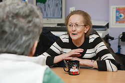 Person with mobility problems in conversation at a resource for people with physical and sensory impairment.