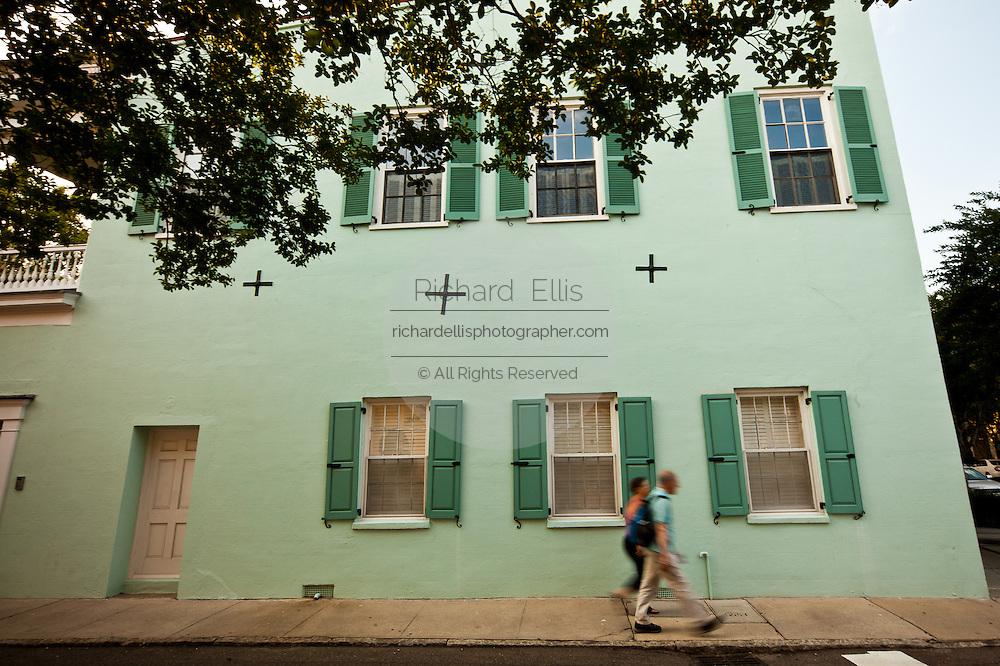 Couple blurred walk past Rainbow row historic houses along Battery Street Charleston, SC.
