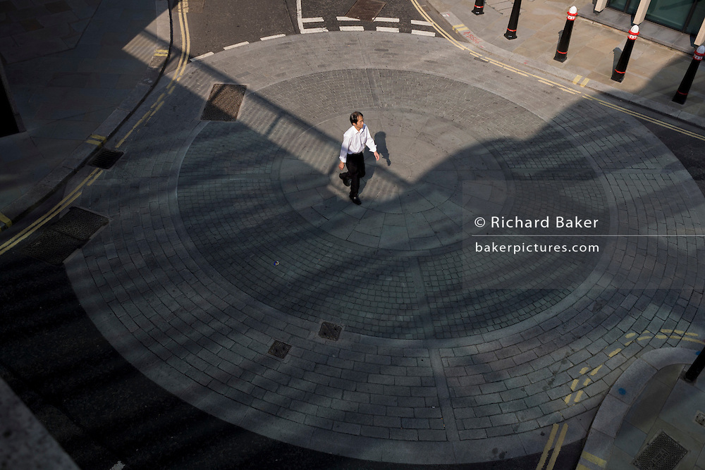 A lone pedestrian over the centre of a mini-roundabout in a City of London side street.