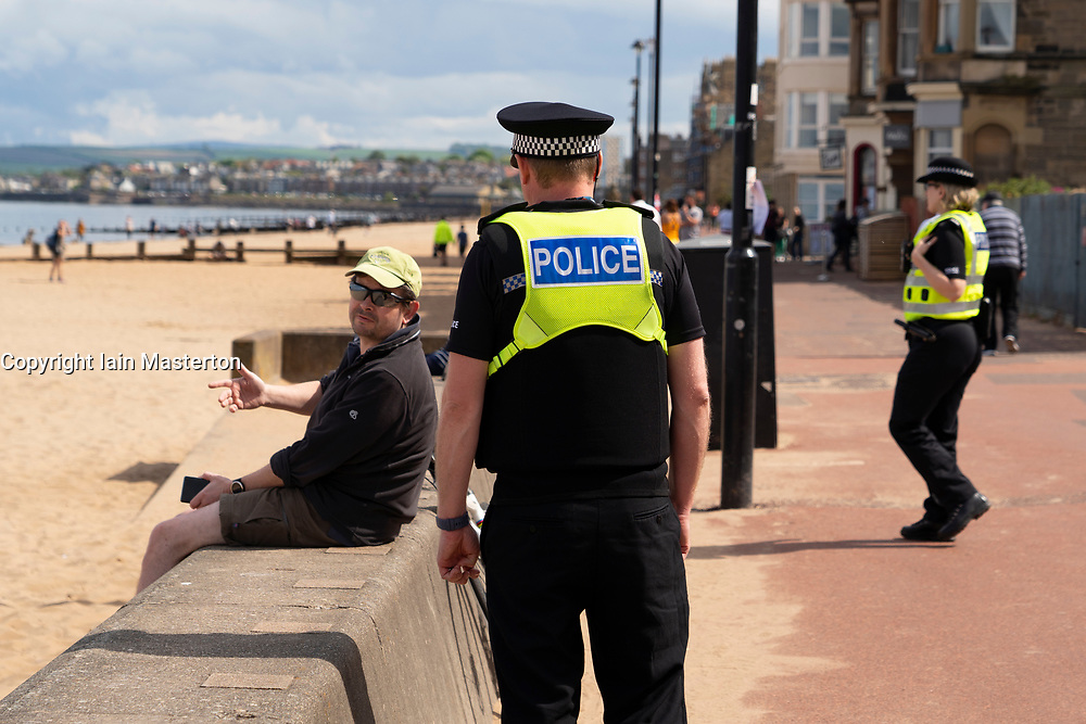 Portobello, Scotland, UK. 9 May 2020. Images from holiday weekend Saturday afternoon during Covid-19 lockdown on promenade at Portobello. Promenade and beach were relatively quiet with a low key police presence. Pictured;  Police approach man sitting on wall to ask him to move. Iain Masterton/Alamy Live News