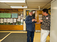 Wayne Ogni stops to chat with Write In candidate Brett Currier on his way to the polls at Gilmanton Elementary School during Tuesday's election.  (Karen Bobotas/for the Laconia Daily Sun)