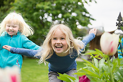 Two blonde kids sisters playing in garden