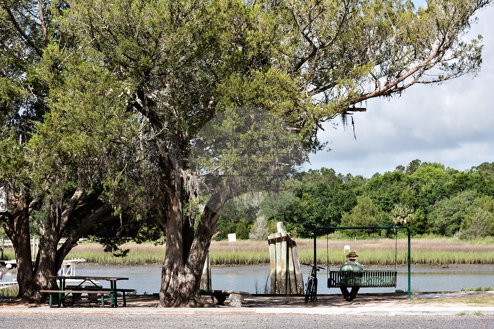 A man sits on a park bench swing along Jeremy Creek in the tiny hamlet of McClellanville, South Carolina. McClellanville is a tiny fishing village inside the Cape Romain National Wildlife Refuge and surrounded by Francis Marion National Forest.
