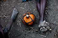 A gourd of milk, sits on the ground between a mother and her child near Boma. During the dry season the women relay on small amounts of milk from the hungry cows and gathered fruit. The nearest hospital is days away.