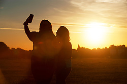 ©Licensed to London News Pictures 30/07/2020     Blackheath, UK. Girls taking a sunrise selfie. Another hot weather day is expected today in the UK as a bright warm sunrise comes up over Blackheath Common this morning in London.  Photo credit: Grant Falvey/LNP