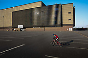 Brent Cross Shopping Centre is nearly deserted during the Coronavirus pandemic on 23th April 2020 in London, United Kingdom. The carpark, normally crowded, is empty apart from young cyclists playing in the afternoon sun, The government clampdown includes the closure of most shops, bars and theatres throughout the country.